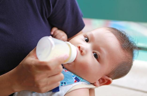 Close-up asian noworodka picia mleka z butelki przez matkę. Premium Zdjęcia