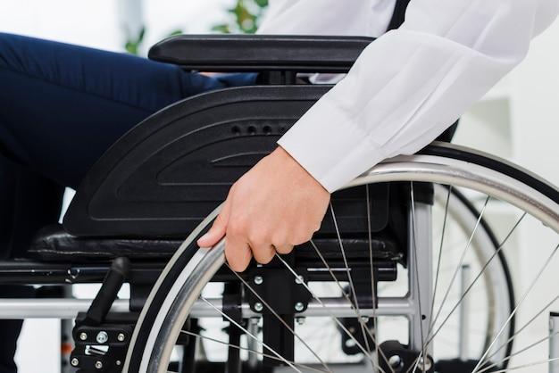Close-up biznesmena ręka na kole wózek inwalidzki Darmowe Zdjęcia