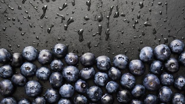 Close-up dojrzałych i soczystych świeżych jagód zebranych z kropli wody. Premium Zdjęcia