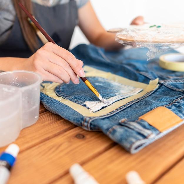 Close-up Kobieta Malowanie Dżinsów Premium Zdjęcia