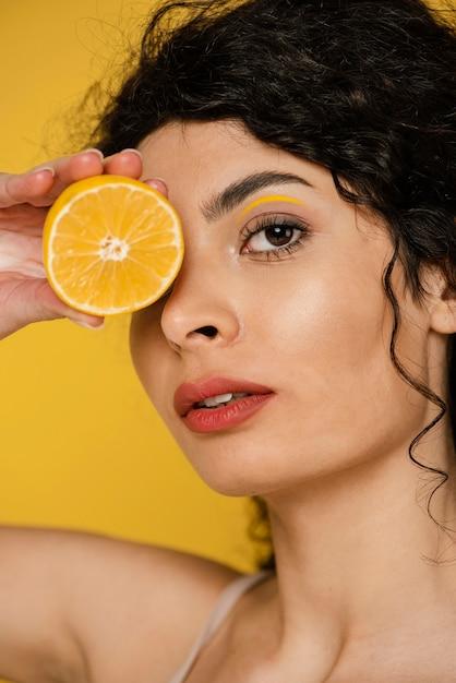 Close-up Kobieta Pozuje Z Plasterkiem Cytryny Darmowe Zdjęcia