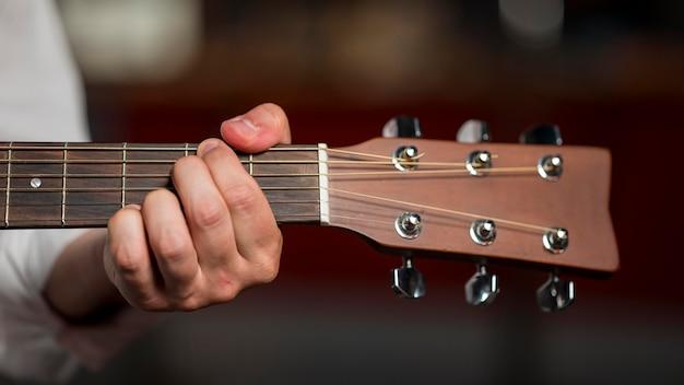 Close-up Mężczyzna Trzyma Akord Na Gitarze Darmowe Zdjęcia