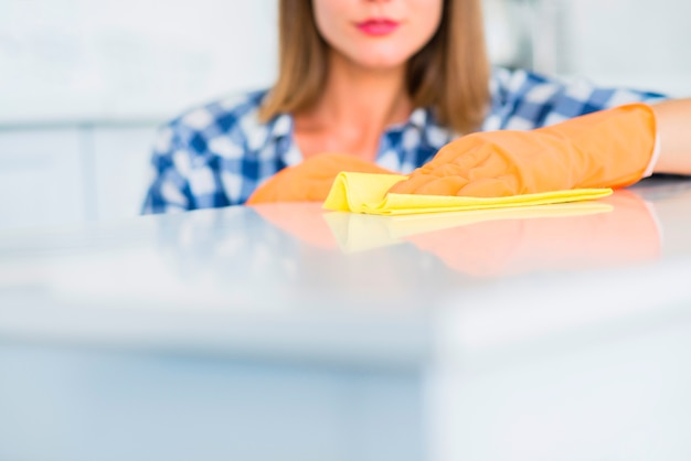 Close-up młoda kobieta czyści białą powierzchnię z żółtym duster Darmowe Zdjęcia