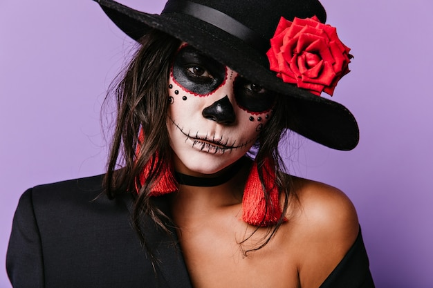 Close-up Portret Meksykańskiej Damy, Która Wykonała Jasny Makijaż Na Dzień Wszystkich Zmarłych. Kobieta Z Czerwonymi Akcesoriami Pozuje Na Liliowej ścianie. Darmowe Zdjęcia