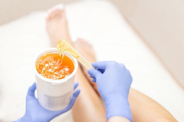Close-up ręce kosmetyczki w niebieskie rękawiczki gospodarstwa wklej dla słodzenia depilacji Premium Zdjęcia
