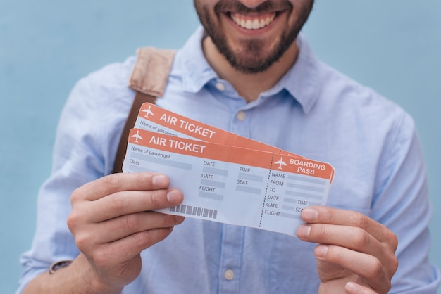 Close-up uśmiechnięty mężczyzna pokazuje bilet lotniczy Darmowe Zdjęcia
