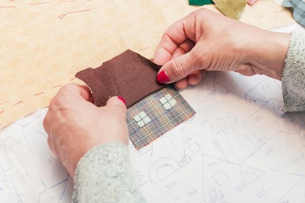 Close-up z kobiecej strony szycia tkaniny w kształcie domu na papierze Darmowe Zdjęcia