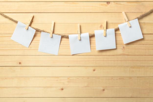Clothespin Obwieszenie Z Pustym Papierem Na Drewnianym Tle Premium Zdjęcia