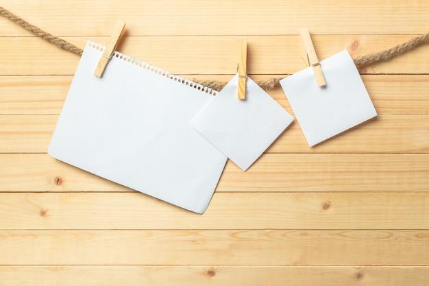 Clothespin Obwieszenie Z Pustym Papierem Na Drewnianym Premium Zdjęcia