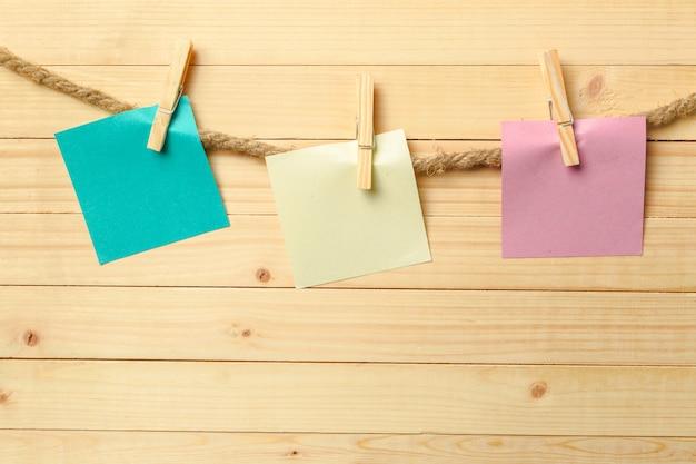 Clothespin Wiszące Z Czystym Papierze Na Drewnianym Stole Premium Zdjęcia