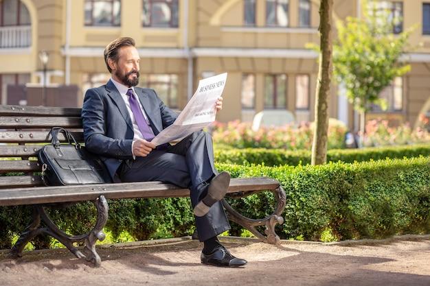 Codzienne Wiadomości. Pełnej Długości Miły, Uśmiechnięty Biznesmen Czytający Gazetę Siedząc Na ławce Premium Zdjęcia