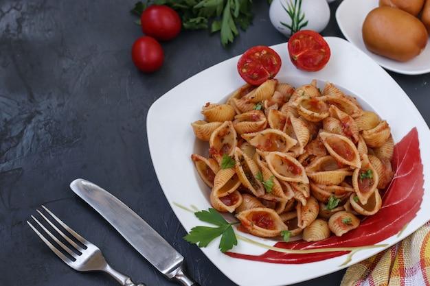 Conchiglie Włoskie Skorupy Makaronu Z Pomidorami Koktajlowymi I Sosem Pomidorowym Na Ciemnym Tle Premium Zdjęcia