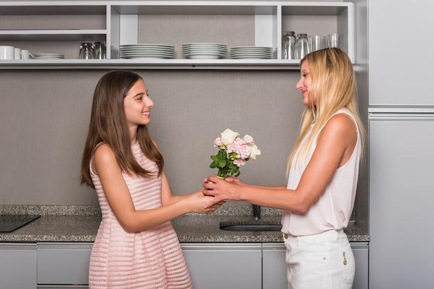 Córka Daje Kwiaty Matka W Kuchni Darmowe Zdjęcia