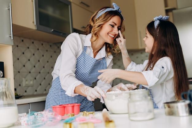 Córka i jej matka bawią się razem podczas pieczenia. Premium Zdjęcia