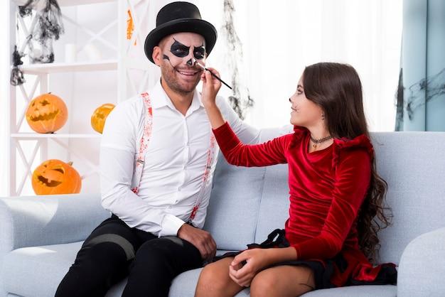 Córka maluje tatusiów twarz na halloween Darmowe Zdjęcia