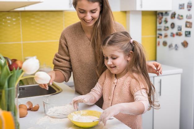 Córka miesza mąkę z jajkami w pucharze Darmowe Zdjęcia