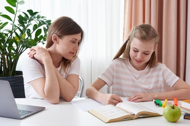 Córka Pomaga Odrabiania Lekcji Matki. Pojęcie Edukacji Domowej W Kwarantannie. Trudności Uczenia Się Na Odległość Premium Zdjęcia