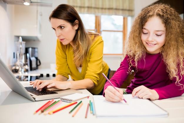 Córka robi jej pracę domową i matkę pracy na laptopie w kitc Darmowe Zdjęcia