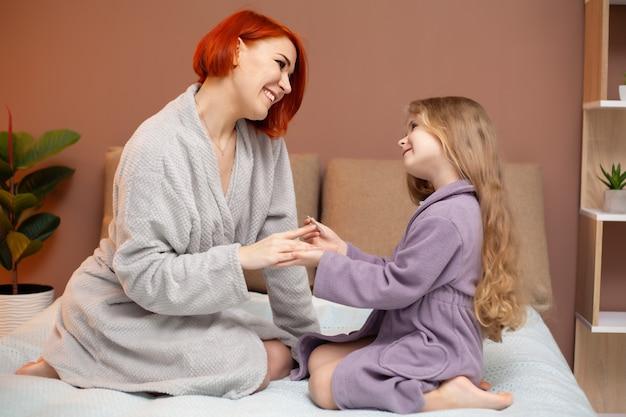 Córka Sprawia, że Mama Robi Manicure W Domu Na łóżku Premium Zdjęcia