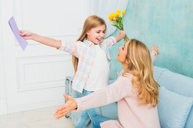 Córka z prezenty kwiat i pocztówka przytulanie matki Darmowe Zdjęcia