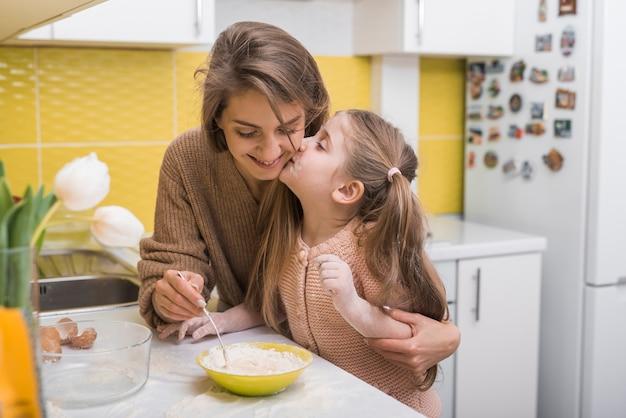 Córki całowania matka podczas gdy gotujący w kuchni Darmowe Zdjęcia