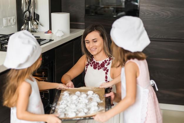 Córki pomaga ich matki mienia ciastka tacę dla piec w kuchni Darmowe Zdjęcia