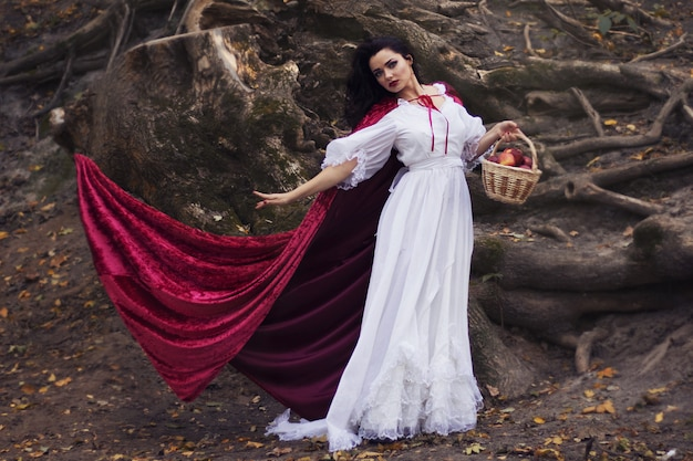 Cosplay Do Bajki Królewna śnieżka, Kobieta W Czerwonym Płaszczu I Wózek Jabłek W Lesie Premium Zdjęcia
