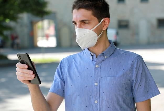Covid-19 Młody Mężczyzna W Masce Ffp2 Za Pomocą Smartfona Na City Street Premium Zdjęcia