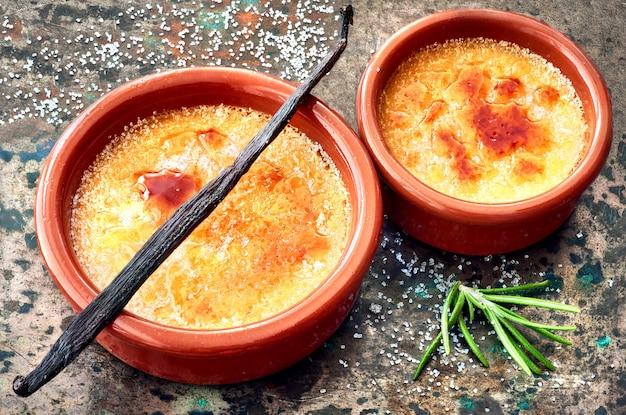 Creme Brulee (krem Brulee, Przypalona śmietana) Z Patyczkiem Waniliowym W Naczyniach Do Pieczenia Terracota Premium Zdjęcia