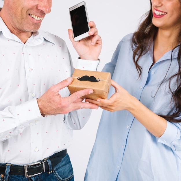 Crop córka daje prezentowi ojciec z smartphone Darmowe Zdjęcia