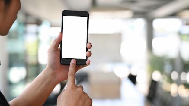 Cropped strzału mężczyzna mienie i dotyk na mockup odizolowywał telefon komórkowego w pokoju. Premium Zdjęcia