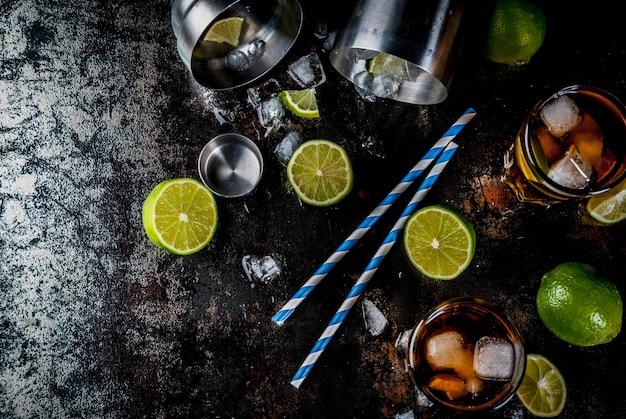 Cuba Libre, Koktajl Z Długiej Wyspy Lub Mrożonej Herbaty Z Mocnym Alkoholem, Colą, Limonką I Lodem, Dwie Szklanki, Ciemny Widok Z Góry Premium Zdjęcia