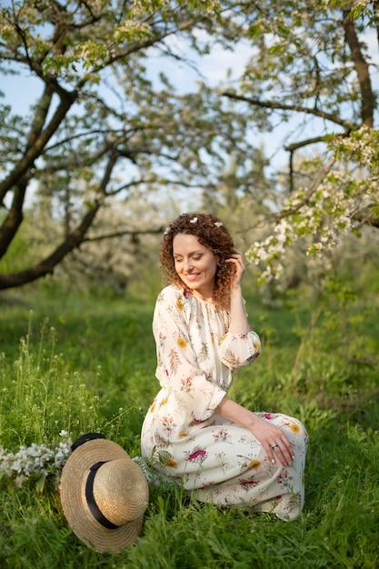 Cudowna Dziewczyna Chodzi Po Kwitnącym Wiosennym Ogrodzie. Pojęcie Jedności Człowieka Z Naturą. Premium Zdjęcia