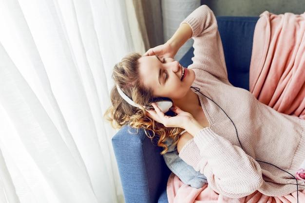 Cudowna Kobieta O Kręconych Krótkich Włosach Słucha Ulubionej Muzyki I Z Przyjemnością Leży Z Zamkniętymi Oczami. Ubrana W Uroczą, Różową Odzież Domową. Darmowe Zdjęcia