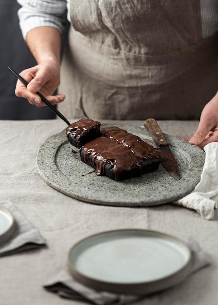 Cukiernik Cięcie I Umieszczanie Ciasta Czekoladowego Na Talerzu Darmowe Zdjęcia