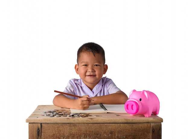 Cute asian country boy zanotuj wpływy z dochodów i monety z piggy bank Premium Zdjęcia