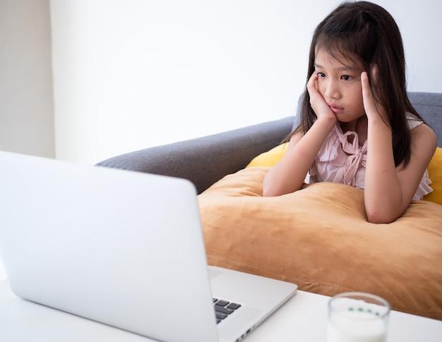 Cute Asian Girl Używa Laptopa Do Nauki Lekcji Online. Premium Zdjęcia
