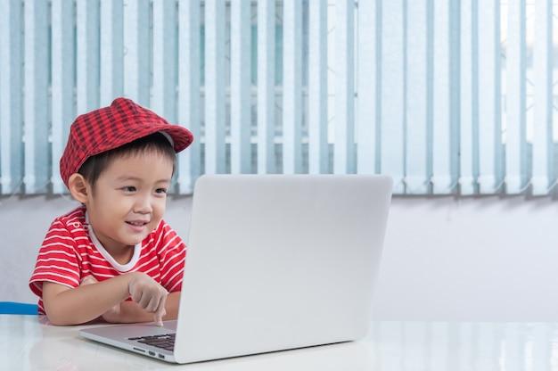 Cute Chłopiec Odtwarzanie Komputera Przenośnego W Pokoju Dla Dzieci Darmowe Zdjęcia
