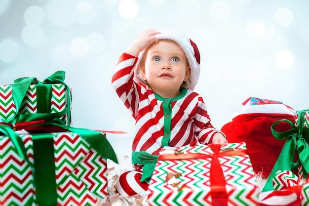 Cute Dziewczynka 1 Rok Na Sobie Kapelusz Santa Stwarzających Nad Ozdoby świąteczne Z Prezentami. Siedząc Na Podłodze Z Bombką Darmowe Zdjęcia