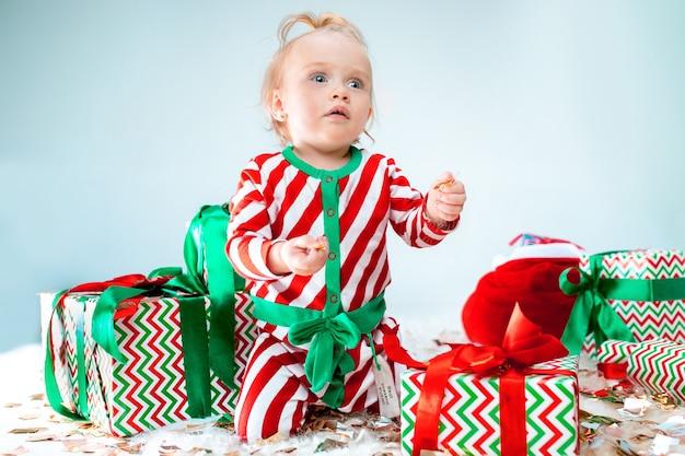 Cute Dziewczynka 1 Rok W Pobliżu Santa Hat Pozowanie Na Tle Bożego Narodzenia. Siedząc Na Podłodze Z Bombką. Sezon Wakacyjny. Darmowe Zdjęcia