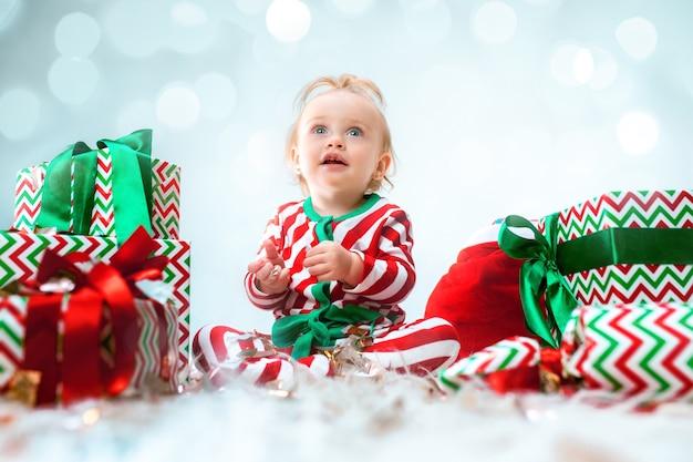 Cute Dziewczynka 1 Rok W Pobliżu Santa Hat Pozuje Na Boże Narodzenie Z Dekoracją. Siedząc Na Podłodze Z Bombką Darmowe Zdjęcia