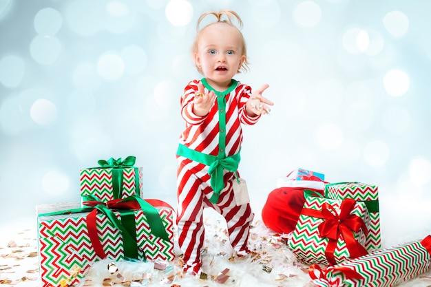 Cute Dziewczynka 1 Rok życia Na Sobie Kapelusz Santa Stwarzających Na Tle Bożego Narodzenia. Stojąc Na Podłodze Z Bombką. Sezon Wakacyjny. Darmowe Zdjęcia