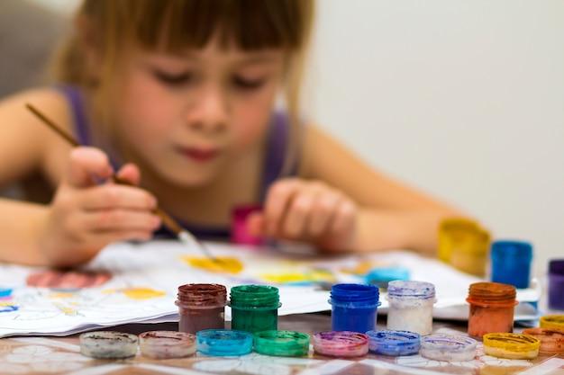 Cute Dziewczynka Malowanie Pędzlem I Kolorowe Farby Premium Zdjęcia