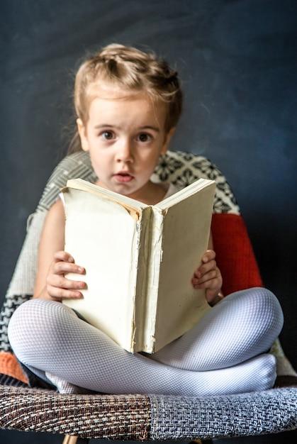 Cute Dziewczynka Siedzi Na Pięknym Krześle Z Książką W Ręku, Pojęcie Edukacji I życia Szkolnego Darmowe Zdjęcia