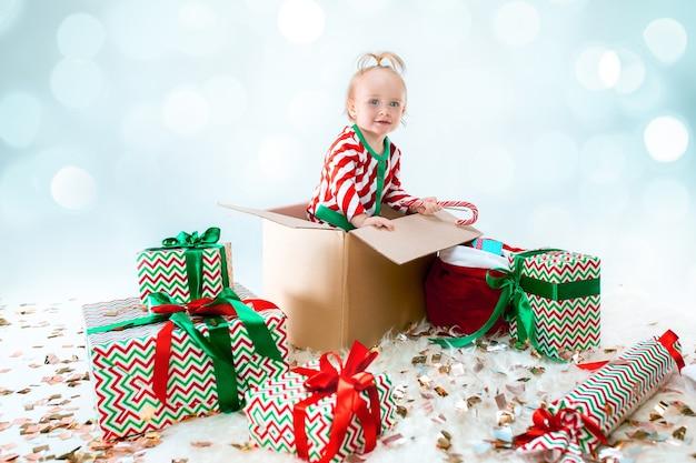 Cute Dziewczynka Siedzi W Polu Na Boże Narodzenie. Wakacje, Uroczystość, Koncepcja Dziecka Darmowe Zdjęcia