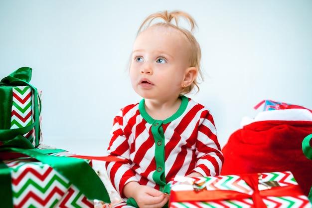 Cute Dziewczynka W Pobliżu Santa Hat Pozowanie Na Tle Bożego Narodzenia. Siedząc Na Podłodze Z Bombką. Sezon Wakacyjny. Darmowe Zdjęcia