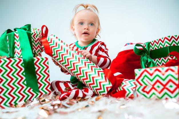 Cute Dziewczynka W Pobliżu Santa Hat Pozowanie Na Tle Bożego Narodzenia Z Dekoracją. Siedząc Na Podłodze Z Bombką. Sezon Wakacyjny. Darmowe Zdjęcia