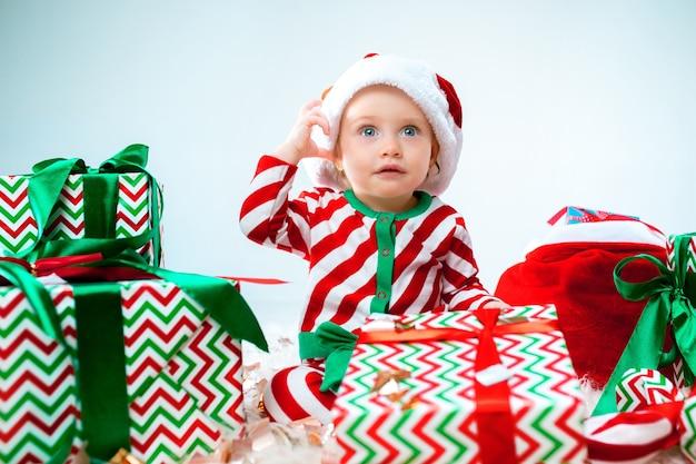 Cute Dziewczynka W Pobliżu Santa Hat Pozowanie Na Tle Bożego Narodzenia Z Dekoracją. Siedząc Na Podłodze Z Bombką. Darmowe Zdjęcia