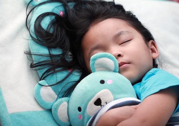 Cute little asian girl spać i przytulić misia Premium Zdjęcia