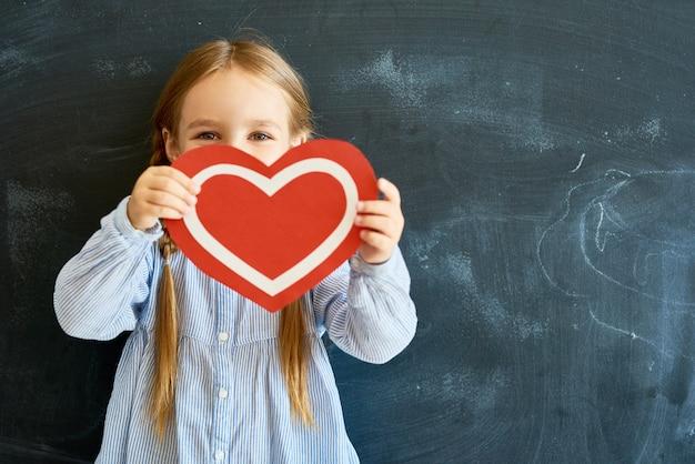 Cute Little Girl Gospodarstwa Papierowe Serce Premium Zdjęcia